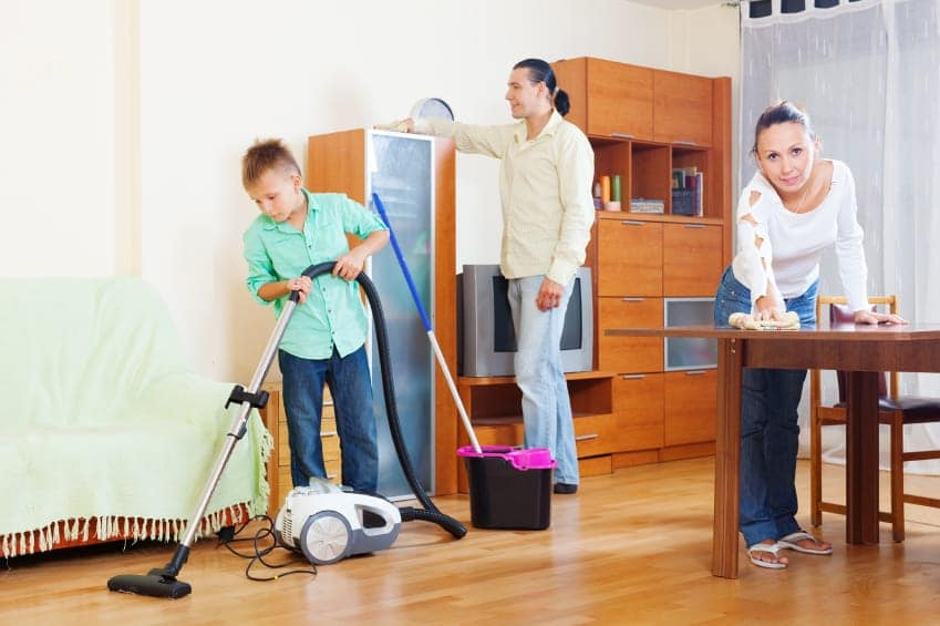 family of three with boy cleaning in room
